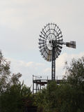 The old wind generator standing in the industrial zone Royalty Free Stock Photo