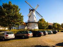 Old wind mill next to the parking lot with a lot of cars in it. Beautiful sunny day and still weather Royalty Free Stock Photography