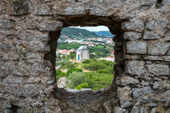 Old wind mill, Obidos (Portugal). View of an old wind mill through a hole in a wall, Obidos (Portugal royalty free stock image