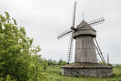 Old wind mill at the park with gray sky clouds Royalty Free Stock Photo