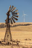 Old wind pump and new wind generators distorted by hot air. South Australia. Royalty Free Stock Photo