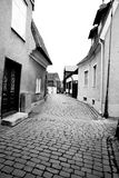 Old winding cobblestone street in black and white. Village views in black and white with cobblestone street Royalty Free Stock Images