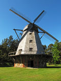Old windmill. On a meadow in the blue sky background Royalty Free Stock Image