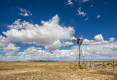 Old Windmill. Old Abandoned Aermotor Metal Windmill Water Pump and Basin With Cloudy Sky Background Stock Images