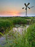 Old windmill in agricultural area Stock Photo