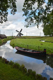 Old windmill and boat on canal Stock Images