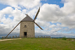 Old windmill in Brittany, France. Old windmill against cloudy sky in Brittany, France Stock Photo