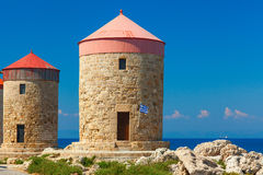 Old windmill buildings with colorful roofs. Rhodes quay Stock Photos