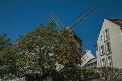 """Old windmill and buildings under sunny blue sky in the Montmartre district at Paris. Known as the """"City of Light"""", is one of the most impressive world's Stock Photography"""