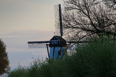 Old windmill with bushes in the late afternoon light and cloudy sky near Bruges royalty free stock images
