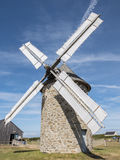 An old windmill on the coast of Normandy. Stone structure, woode. N gears and bare white coated blades Royalty Free Stock Images