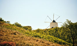 Old windmill in countryside. Scenic view of old windmill in countryside, hillside in foreground Stock Image