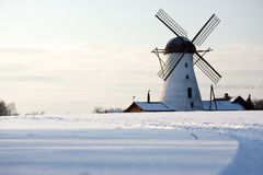 Old windmill in Estonia. A photo of an old windmill behind the snow field at winter Royalty Free Stock Photography