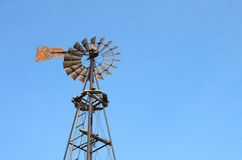 Old Windmill. An farm windmill as seen against a bright blue sky Stock Images