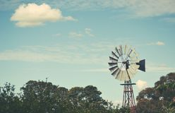 Iconic old Australian windmill background. Old windmill on farmland surrounded by trees under a blue cloud filled sky in Orange, country NSW, Australia. Retro Stock Images