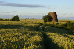 Old windmill in field Stock Photo