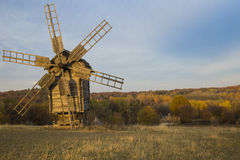 Old windmill in a field near the forest at sunset Stock Photos