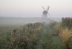 Old windmill in foggy countryside landscape in England Royalty Free Stock Image