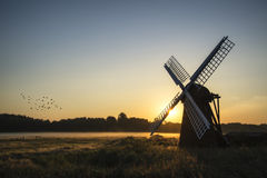 Old windmill in foggy countryside landscape in England Royalty Free Stock Photo
