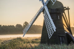 Old windmill in foggy countryside landscape in England Stock Photos