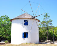 Old windmill in Greece. View of the old windmill in Greece in the background with trees Royalty Free Stock Photography