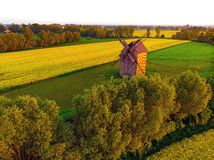 Old windmill and green fields. Old windmill green fields agriculture country countryside trees farms yellowflowers spring springtime landscapes view mokrydwor royalty free stock images