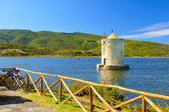 Old windmill in harbor of orbetello Royalty Free Stock Image