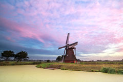Old windmill by lake at sunrise Stock Photography