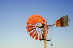 Old windmill. With metal vanes for pumping water on a rural farm using the kinetic energy of the wind against a clear blue sky Royalty Free Stock Photo