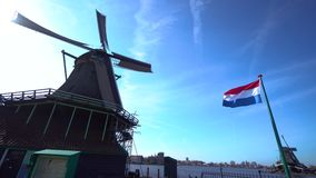 Zaanse Schans Windmill against a clear sky in the Netherlands. The old windmill near which stands the flag of the Netherlands, is shot against the background of stock video footage
