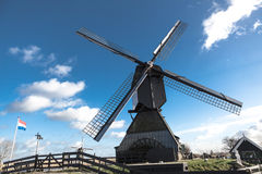 Old windmill with the Netherlands flag. White clouds on a blue sky, the wind is blowing. Stock Photo