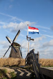 Old windmill with the Netherlands flag. White clouds on a blue sky, the wind is blowing. Stock Images