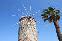 Old Windmill and Palm Tree. Of Rhodes Island,Greece stock photo