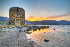 Old windmill ruin on Crete at sunset. Old windmill ruin at Mirabello Bay on Crete, Greece Stock Images