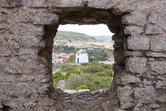 Old windmill through small window in fortress wall, Obidos Stock Photos