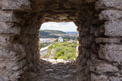Old windmill through small window in fortress wall, Obidos Royalty Free Stock Photography
