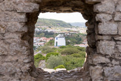 Old windmill through small window in fortress wall, Obidos Stock Images