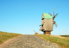 Old windmill and stone road. Antique wooden windmill and stone road, Pirogovo, Kiev, Ukraine Royalty Free Stock Images