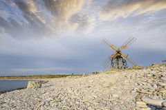 Old windmill on stoney beach Stock Image