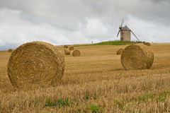 Old windmill in a straw bales field  in France. Old windmill in a cultivated  straw  field with bales in Brittany, France Stock Images