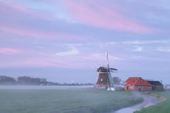 Old windmill in sunrise fog by river Royalty Free Stock Photos