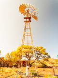 Old windmill water pump in dry landscape. Metallic tower construction Royalty Free Stock Photos
