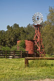 Old windmill and water tank. A view of an old red wooden windmill and water storage tank in a country setting Stock Images