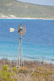 Old windmill on waters edge. Vintage windmill spinning at shore with turquoise water near Esperance, Western Australia Royalty Free Stock Photo
