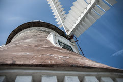 Old windmill. In wheel in front of the blue sky Royalty Free Stock Images