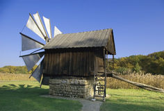 Old windmill wodden house and fabric blades. Beautiful late evening light open-air museum Sibiu Romania Royalty Free Stock Image