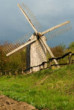 Old windmill and wooden fence. Very old wooden fence and old windmill on a green field near wood Royalty Free Stock Photo