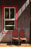 Old window with 2 steal chair Royalty Free Stock Photos