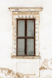 Old window. Old grunge mosaic window on a white cracked wall Royalty Free Stock Photo