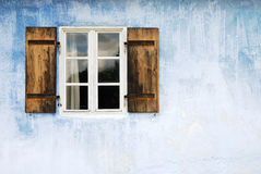 Old window. On a blue wall stock photo